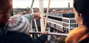 Eine Familie auf dem Riesenrad in Fürth zeigt auf SEO Agentur